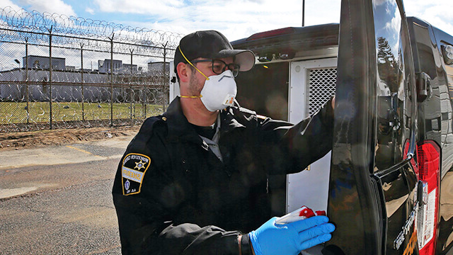 A correctional officer taking measures to fight against COVID-19 by sanitizing an inmate van.