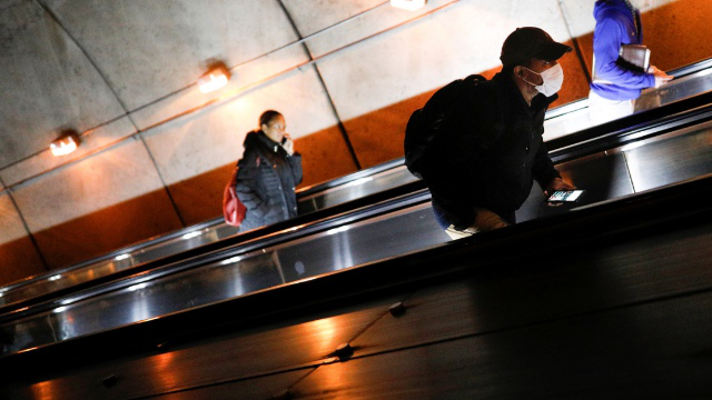 Three people on the escalator in a Washington D.C. metro station.