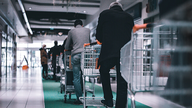 Grocery shoppers st和ing in line at a social distance.