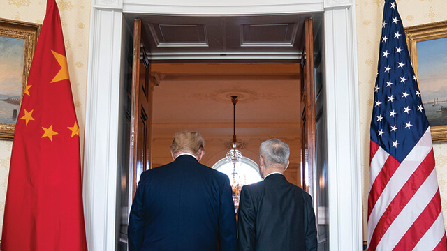 President Donald J. Trump 和 Chinese Vice Premier Liu He walk through a doorway at trade negotiations in January.