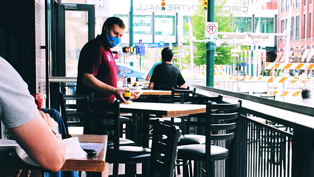 A restaurant worker in a protective mask prepares table for outdoor seating.