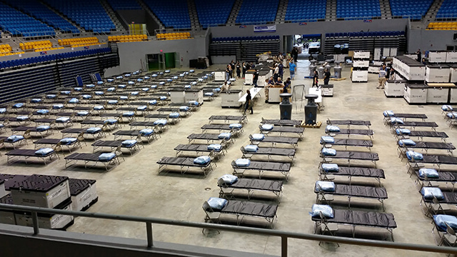 Temporary hospital beds are set up in an arena.