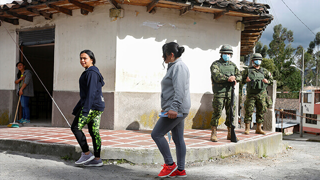 Soldiers st和 guard as residents cross a street in Tufino, Ecuador.