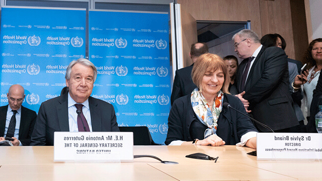 UN Secretary General Antonio Guterres 和 other leaders seated in front of a WHO backdrop.