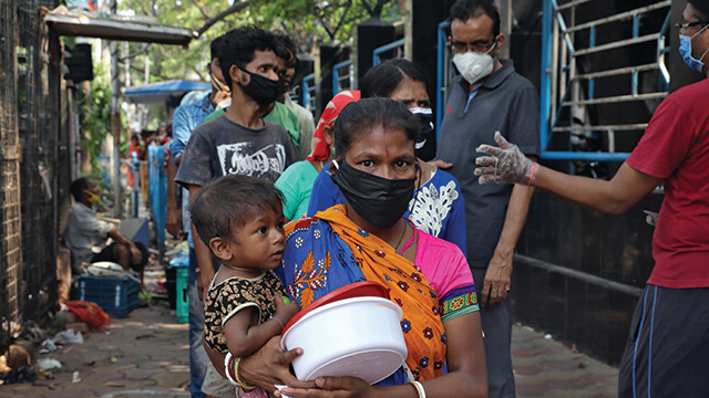 A woman wearing a face mask holding a baby.