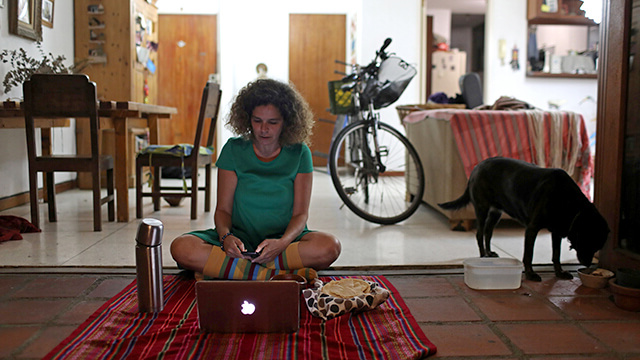 A woman uses her computer to go online 和 join a virtual picnic with her friends at her home.