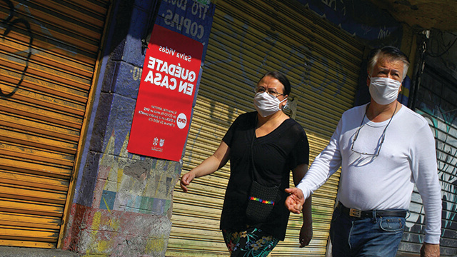People wearing protective masks pass in front of a sign that reads 'Stay at home' during the coronavirus disease outbreak, in Mexico City.