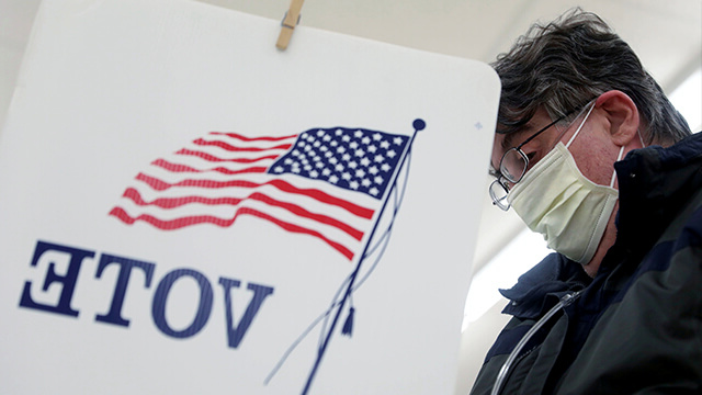 A voter, wearing a protective mask, fills out his ballot during the primary election in Illinois in March.