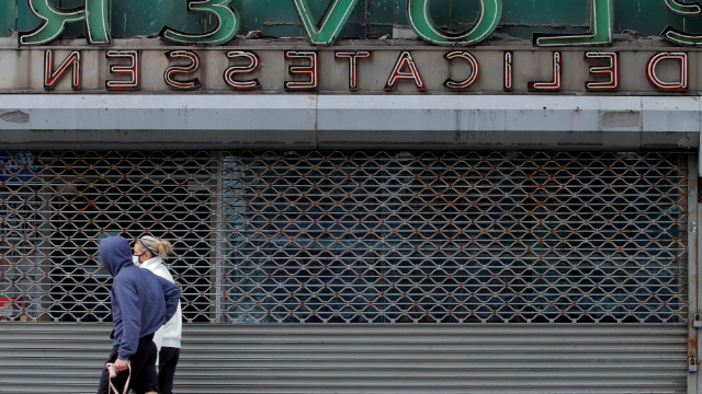 People pass by a closed delicatessen, during the outbreak of the coronavirus disease in New York City.